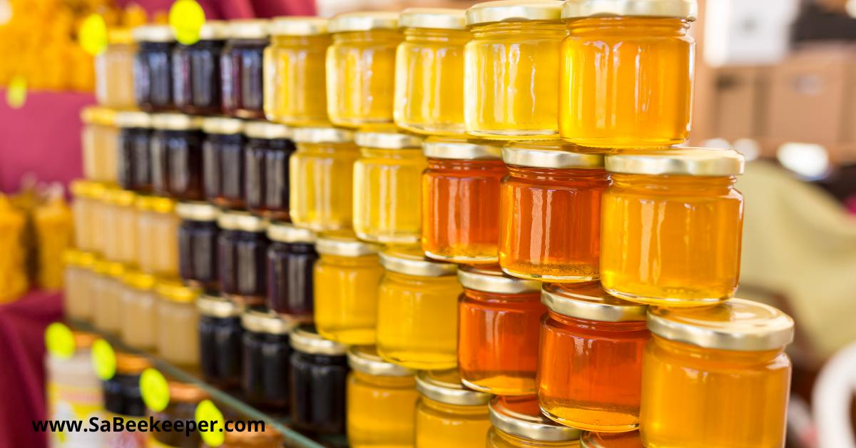 different colors of honey in honey jars. from light to dark honey.