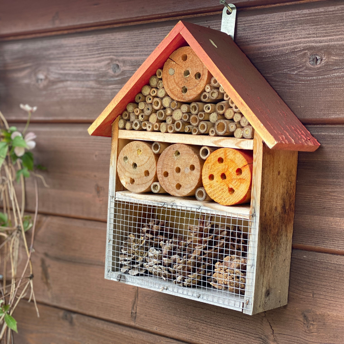a bee hotel on a side of a wooden shed of the ground.
